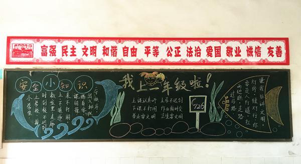 图为育才小学开学安全宣传黑板报,二十四字核心价值观都是剪纸作品